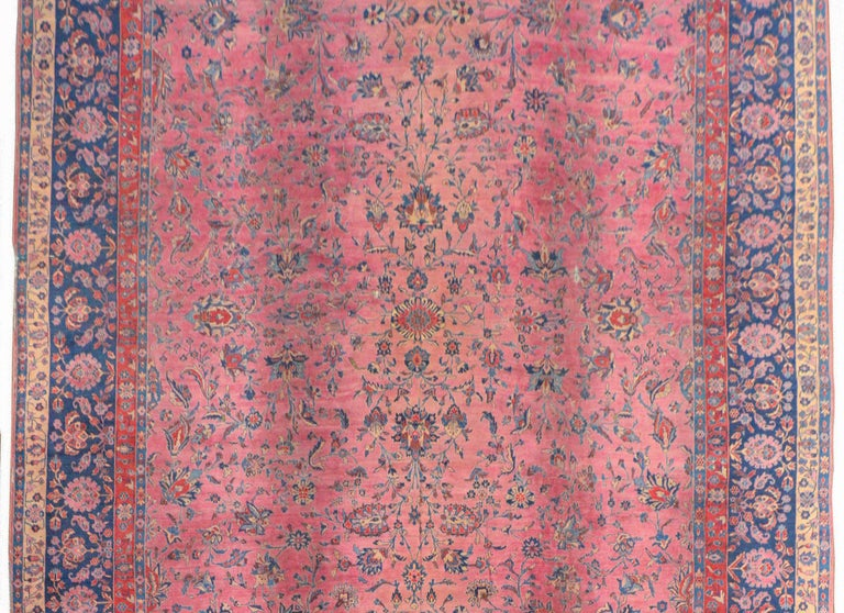 A gorgeous early 20th century Persian Sarouk rug with a fantastic fine all-over large-scale floral and scrolling vine pattern woven in light and dark indigo, coral, brown, against an abrash fuchsia background. The border is extraordinary, with a