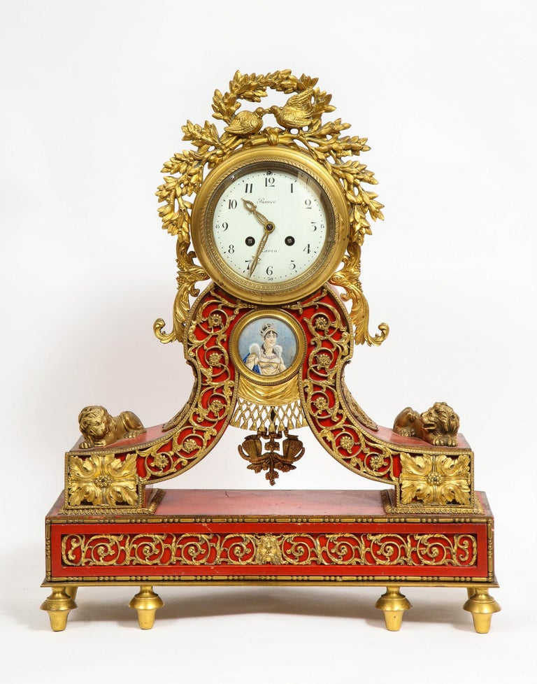 Gorgeous French ormolu gilt bronze-mounted red painted mantel clock, 1870  Clock dial signed Bauce Paris, with Arabic numerals, in a Red case surmounted by love birds within ribbon tied flowering boughs, centered by a portrait miniature of