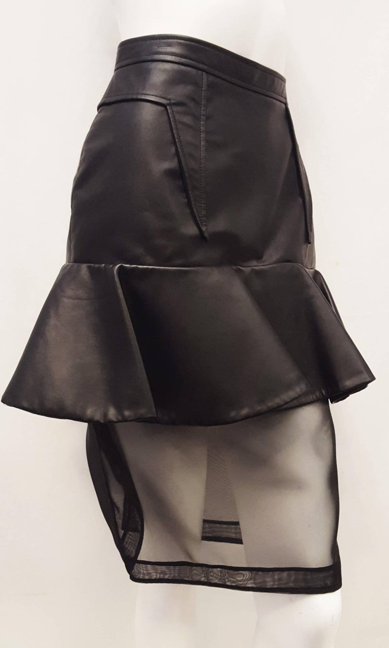 Givenchy features a one-of-a-kind black leather skirt tight to hip with one 7 inch ruffle all around for additional flare.  Below the ruffle is a pencil skirt style mesh under skirt that is transparent so your legs show through.  There is a slit