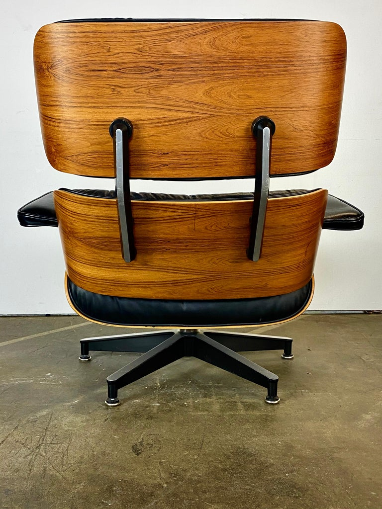 Classic Eames lounge chair and ottoman. Executed in black leather and rosewood shells. Signed on chair and ottoman and guaranteed authentic. No missing buttons or screws. Glides on chair and ottoman. Are adjustable in case the floor or carpet is