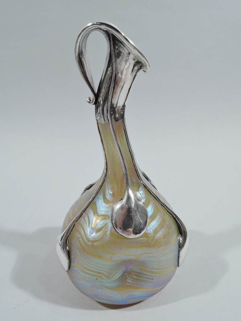 Turn-of-the-century Art Nouveau glass vase by historic maker Loetz with silver overlay. Pinched and globular bowl with curved cylindrical neck. Mouth has silver mount suggestive of a calla lily. Silver drip tendrils terminating in teardrops. Glass