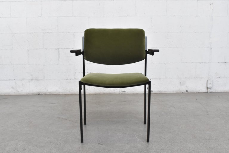 Square black metal frame with olive velvet upholstered seating and solid teak arm rests. Seat width is 17.5 inches. Stackable. In good original condition with some signs of wear to frame. Priced individually.