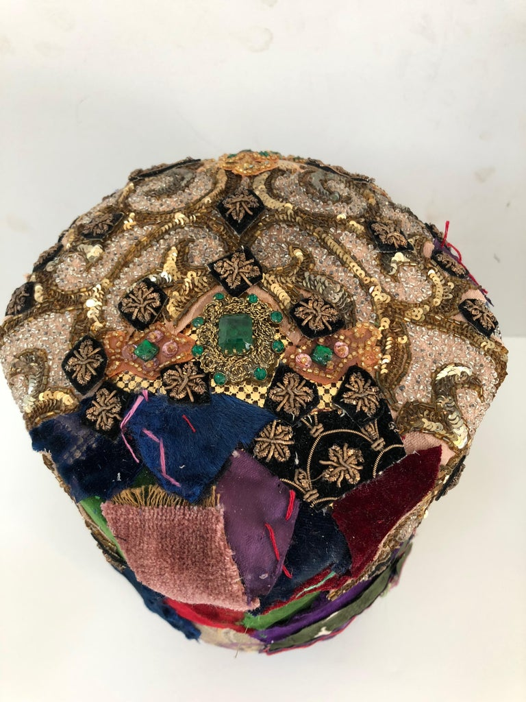Beautifully handmade found object sculpture that originated as a vintage wood rotating hat form, and has been transformed into a sumptuous work of art. The head and base is meticulously collaged with pieces from a velvet crazy quilt, silver and gold
