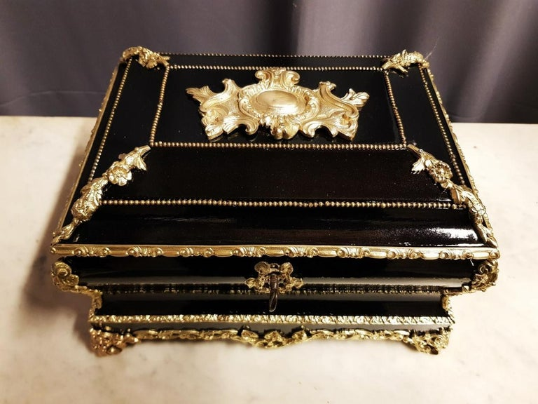 Large Napoleon III style jewelry decorative box Casket of formate form with a rich ornamentation of gilt bronzes. It rests on 4 bronze feet, two bronze handles on the flanks. Red felt interior. Original key that works perfectly. Very