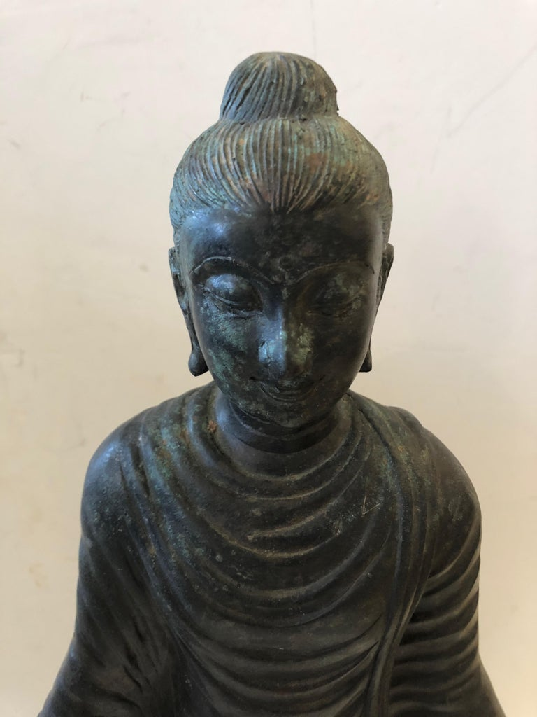 A beautiful medium sized bronze Buddha with some natural verdigris patina. The gestural hands are beautifully placed, and the meticulous detailing is impressive.