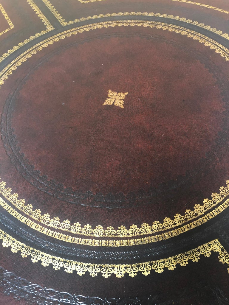 Marvelous round leather wrapped center table having amazing gold tooled decoration everywhere, beautiful brass paw feet on casters, pedestal base with four splayed legs, and 4 drawers around the periphery.