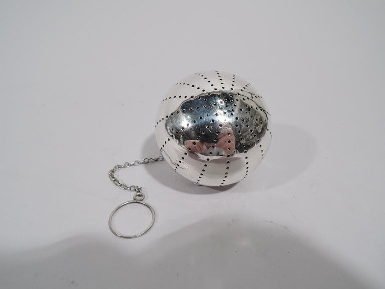 Modern sterling silver tea ball. Made by Gorham in Providence, circa 1920. Globular; cover hinged with loose-mounted chain. Piercing in Classical gadroon pattern. Fully marked including no. 35 and indistinct date symbol.   Ball diameter: 2 in.