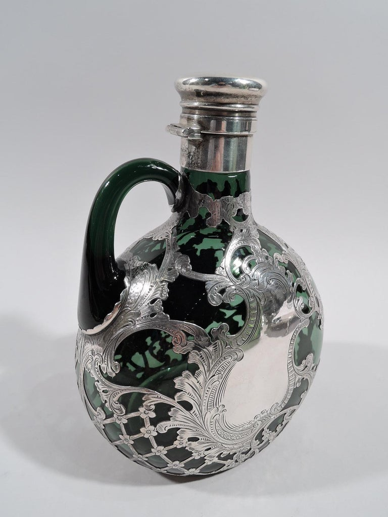 Turn-of-the-century Art Nouveau glass jug decanter with silver overlay. Made by Gorham in Providence. Round with flat front and back; neck cylindrical with sterling silver collar and hinged and cork-lined cover. Loose and meandering leafy scrolls,