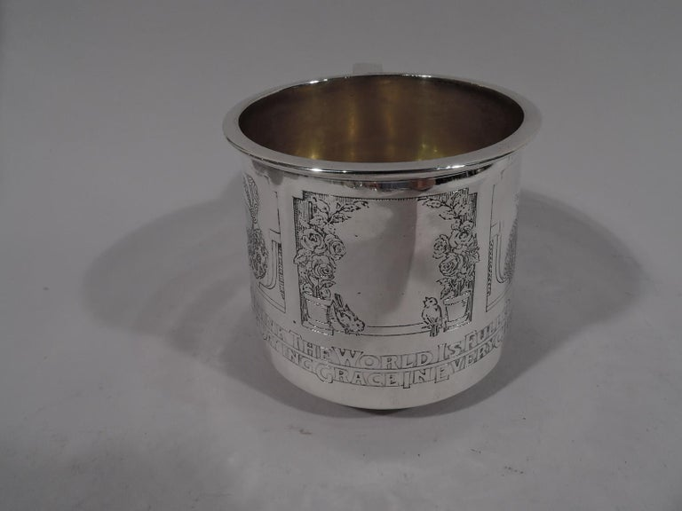 Edwardian Sterling silver baby cup. Made by Gorham in Providence, circa 1910. Gently upwards tapering sides, scrolled bracket handle, and flat rim. Gilt-washed interior. Two acid-etched frames with little girls from around the world (each in
