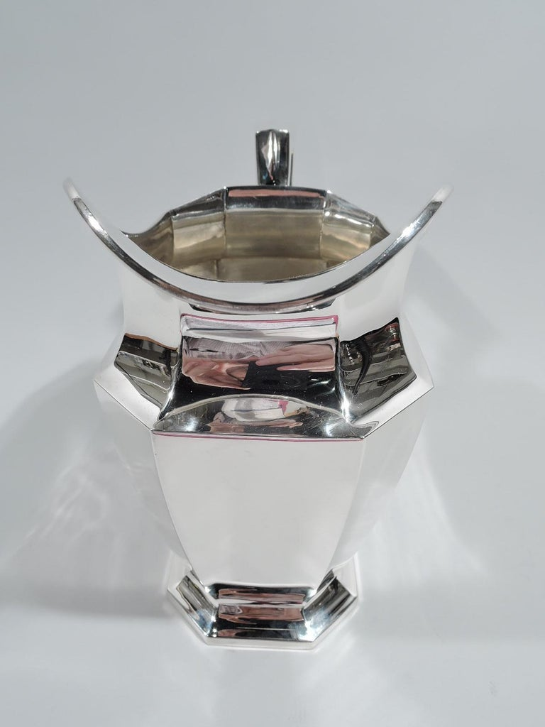 Fairfax sterling silver water pitcher. Made by Durgin (part of Gorham) in Concord, New Hampshire, ca 1920. Faceted with rectilinear body and raised foot, and helmet mouth. Scroll-bracket handle. A desirable piece in the classic Art Deco pattern.