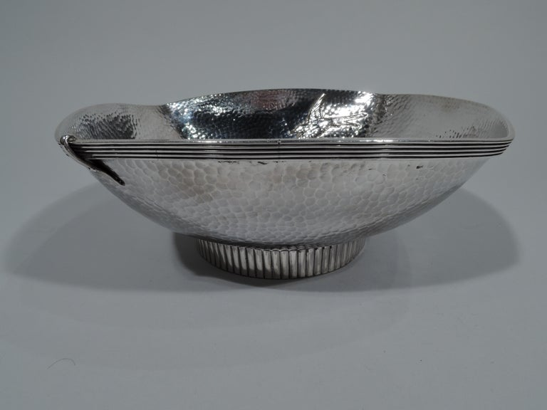 Japonesque sterling silver bowl. Made by Gorham in Providence in 1879. Four curved sides and short round ribbed foot. A pair of humming birds with flapping wings go beak-to-beak perched on a leafy branch. A third flies solo. Hand-hammered honeycomb
