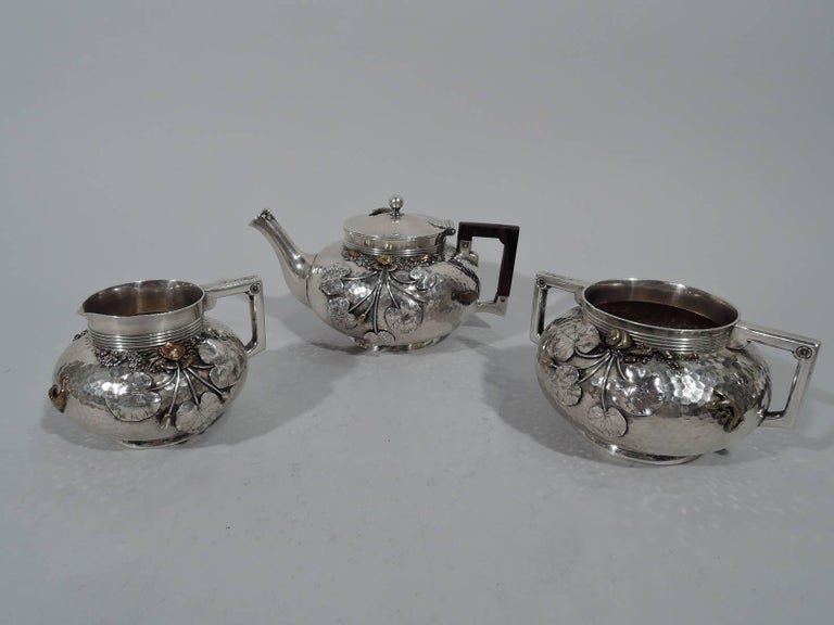 Japonesque sterling silver and mixed metal tea set. Made by Gorham in Providence in 1879-1880. This set comprises teapot, creamer, and sugar.  Each: Bellied with short reeded neck and foot ring. Bracket handles (teapot handle stained wood). Teapot