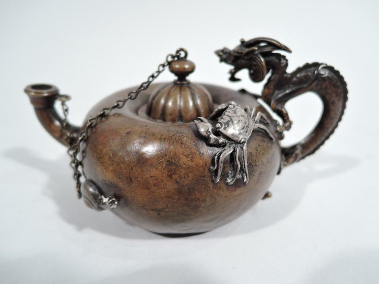 Japonesque mixed metal cigar lighter. Made by Gorham in Providence in 1905. Copper saki-pot form with bellied body and cast handle in form of dragon with horned head and talons gripping sides. Upturned spout. Domed and lobed cover chained to spout.