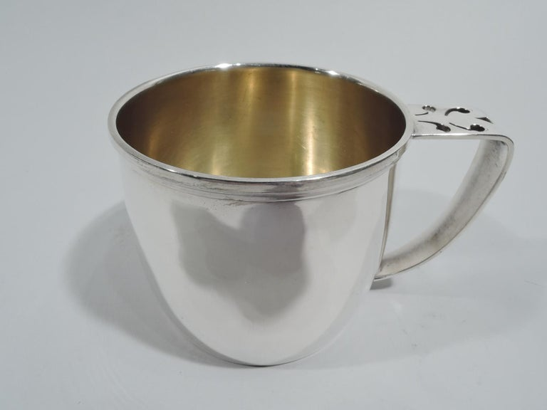 Craftsman sterling silver baby cup. Made by Gorham in Providence, ca 1920. Gently curved sides and molded rim. Scroll-bracket handle with pierced ornament. Gilt-washed interior. Sturdy proportions with plenty of room for engraving. Fully marked