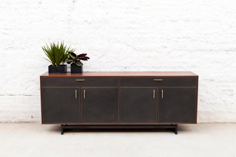The Gotham credenza features clean lines that blend harmoniously with the beautiful mix of materials. A walnut frame sits on a blackened steel base. Custom hand-sculpted bronze pulls compliment the striking blackened bronze encased in resin drawer