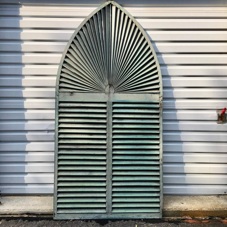 Large size fan louvered exterior window shutter in original rustic distressed old paint, green on front, black on verso. 91 inches tall by 45.5 inches wide. The arched portion begins 52 inches from the bottom. This was removed from a Victorian house
