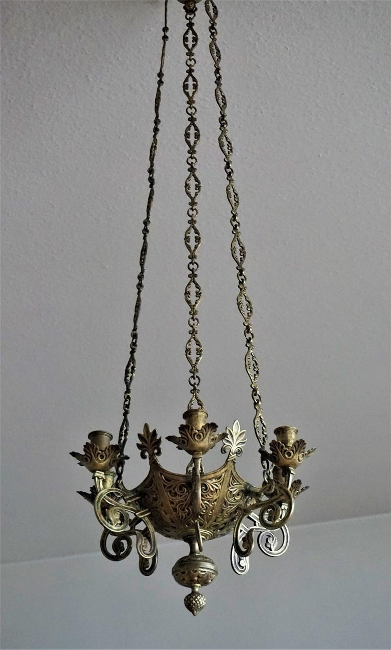A Gothic Revival style bronze and parcel-brass church candle chandelier / hanging sanctuary lamp, Spain, mid-18th century, probably from a family with a private chapel. Crown shape body surrounded by six candle holders. Three long bronze chains