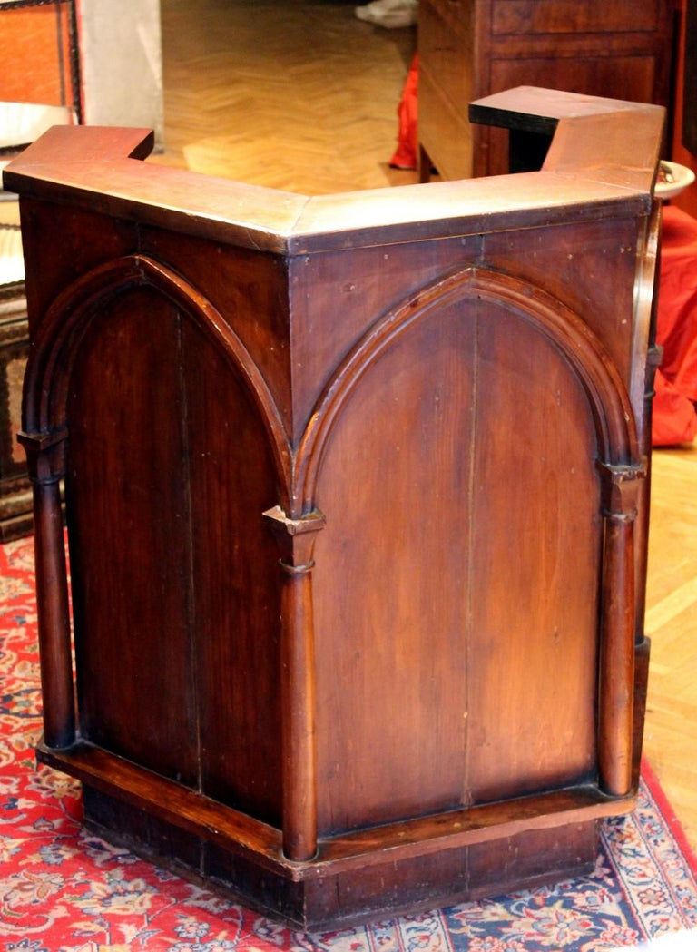 This antique Italian walnut wood pulpit is an outstanding and rare Gothic Revival piece of furniture from late 19th century architecturally shaped with columns and broken arches. The Neo Gothic pulpit is built in the form of a pentagon made up of
