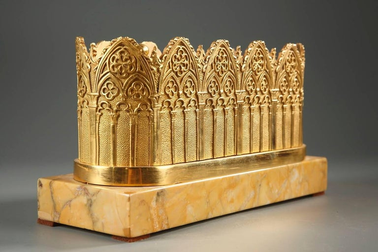 Oval gilt bronze inkwell in Neo-Gothic style, decorated with cathedral arcades and rosettes. It houses two inkwells with their lids and a pounce pot decorated with openwork branches, as well as four pen holders. The inkwell rests on a rectangular