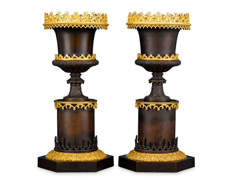 A striking pair of bronze urns, created in the dramatic Gothic style. Resembling classical Greco-Roman vases set upon pedestals, the urns are crafted in a two-toned design, with deep burnished bronze bodies and three galleries of ornate bronze