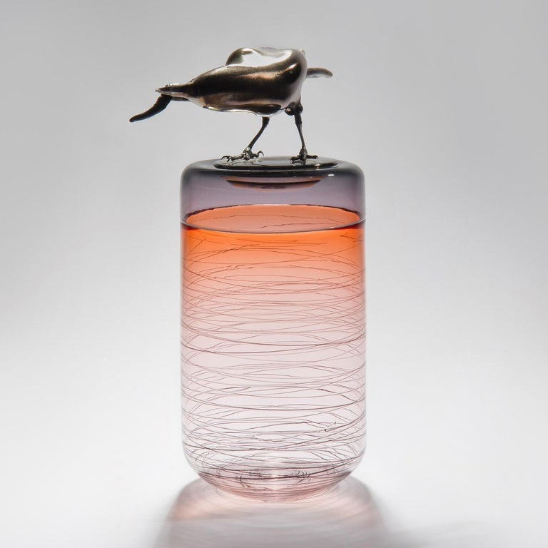 Gourmande, is a hand blown art glass vase in apricot with a removal lid adorned with a hot sculpted black glass crow holding a worm by the British artist Julie Johnson. The crow figurine can also be lifted off with the main body leaving a
