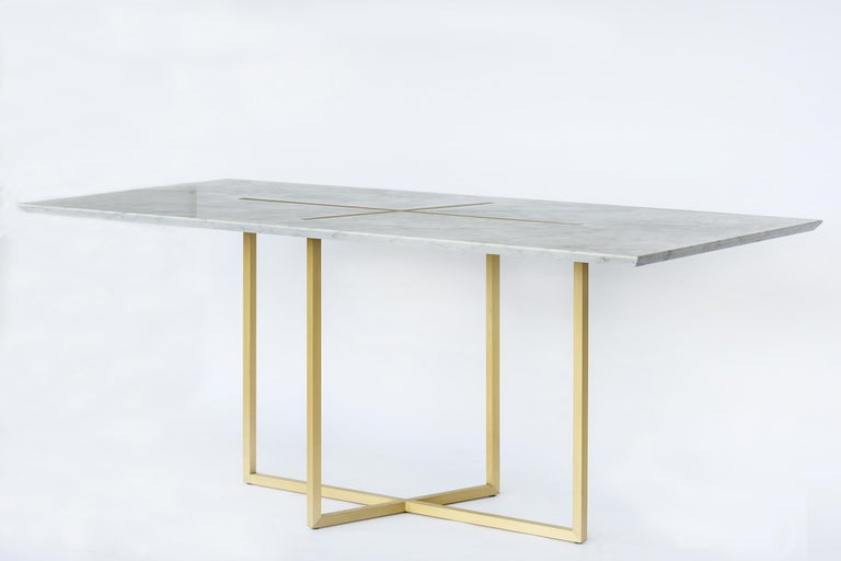 Stunning dining table in authentic Carrara marble of the colors of planets that are crossed by a ray of sunshine in gold brushed brass in the middle.