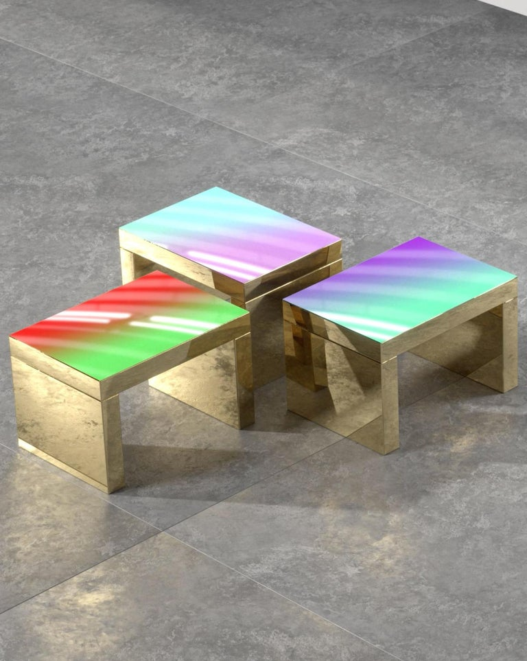 Gaby is a contemporary coffee table that presents shades of color integrated in the table top, which is paired with a chunky and highly reflective gold metallic base. 