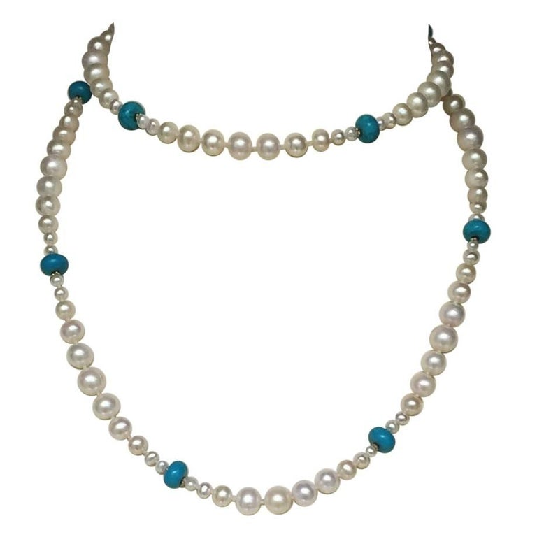 This beautiful necklace has graduated pearls with brilliant blue turquoise and 14 k yellow gold beads with a tassel. The pearls glow in contrast to the turquoise and small gold beads with a 14 k gold clasp. The removable tassel also has graduated