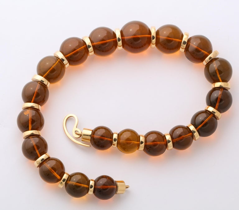 Magnificent reconstituted  polished  Amber Beads ranging from 18 to 25 mm - and separated by 18t Yellow Gold Rondels measuring from  11 to 16 mm x 3 mm The Beads are terminated by cylindrical ends  and a free-form 18kt Yellow Gold Clasp. Very bold
