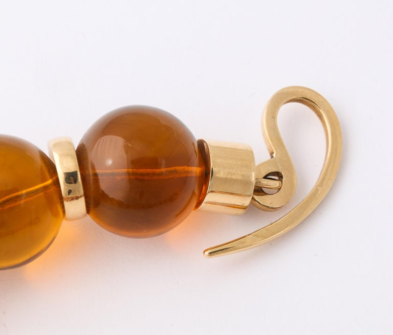 Contemporary Graduated Reconstituted Amber and 18 Karat Yellow Gold Rondel Necklace For Sale