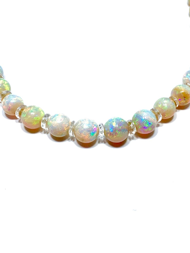 An absolutely stunning graduated white Opal bead necklace.  The play of color within these Opals is comparable to none.  The Opals are strung together with a Rock Crystal Quartz rondelle in between each bead and a 14 karat yellow gold tongue and