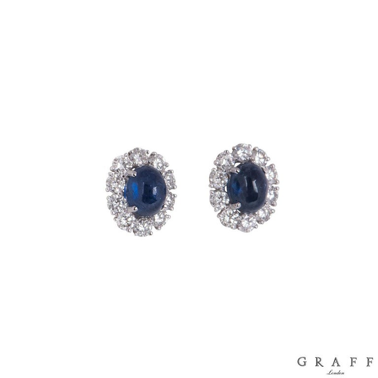 An 18k white gold pair of diamond and sapphire earrings by Graff. The earrings comprise of an oval shaped blue sapphire in the centre within a four claw setting with a halo of 10 round brilliant cut diamonds. The sapphires have an approximate total
