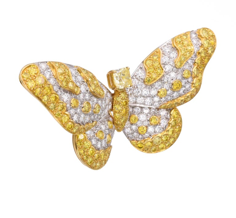 GRAFF This brooch has a fancy intense yellow cut- cornered square modified brilliant -cut diamond of 1.17 carats  Color: Fancy Intense Yellow,  natural color, VS2 clarity, GIA#XXXXXXX), circular-cut diamonds and yellow diamonds, platinum and gold.