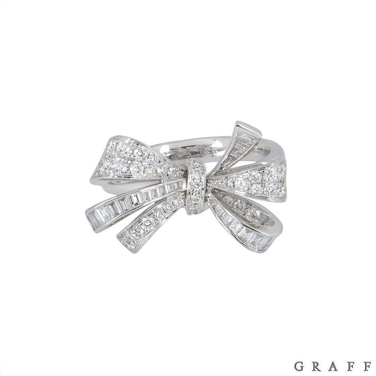 An 18k white gold diamond ring by Graff from the Bow collection. The ring features a bow design set with round brilliant cut and baguette cut diamonds. The round brilliant cut diamonds have an approximate weight of 0.70ct and the baguette cut