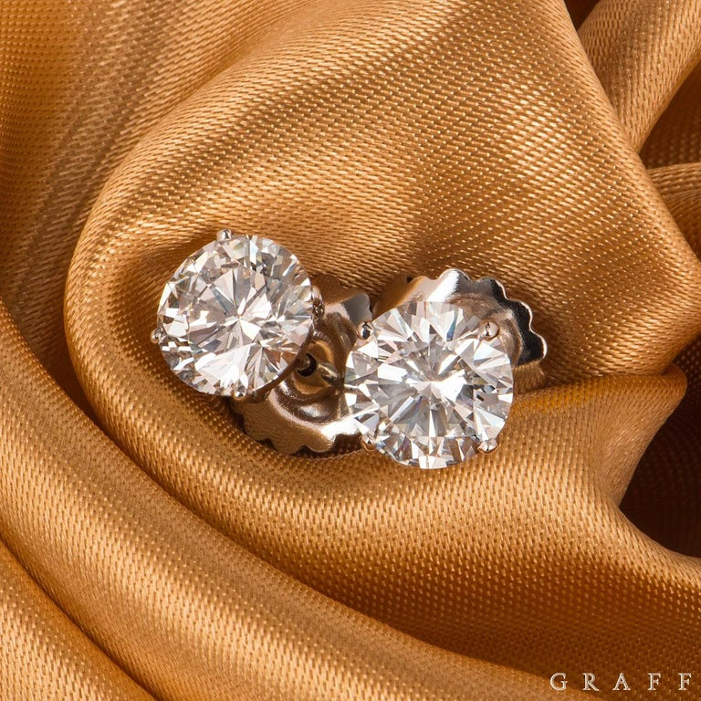 A stunning pair of diamond platinum earrings by Graff. The earrings are set with a round brilliant cut diamond in a 4 claw setting. The earrings are both 2.14ct each, H colour, one earring with VS1 clarity and the other VS2. The earrings feature a