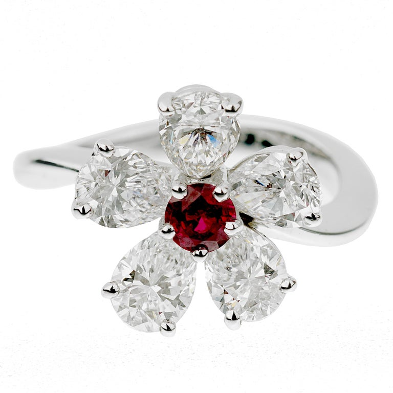 An authentic Graff cocktail ring showcasing 5 pear shaped diamonds (2.65ct appx) surrounding a ruby measuring .25ct appx designed in a floral motif. The ring is crafted in platinum and in excellent condition. The ring measures a size 6 and can be