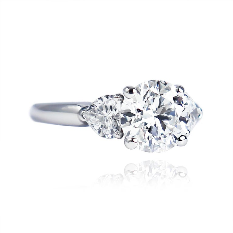This romantic, three-stone ring from the house of GRAFF features a GIA certified round brilliant diamond of F color and VVS2 clarity with excellent cut, polish, and symmetry. Flanked by a pair of heart shape side stones = approximately 0.60 carat