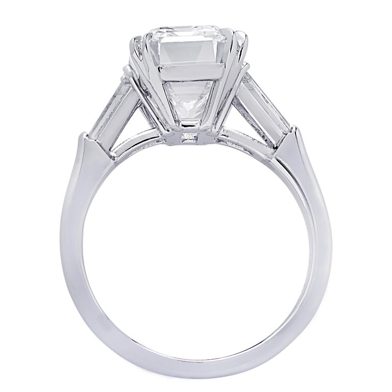 From the renowned House of Graff, this sensational engagement ring, finely crafted in Platinum, showcases a spectacular GIA Certified Emerald Cut Diamond weighing 5.08 carats, D color, Internally Flawless. This stunning diamond is adorned with two