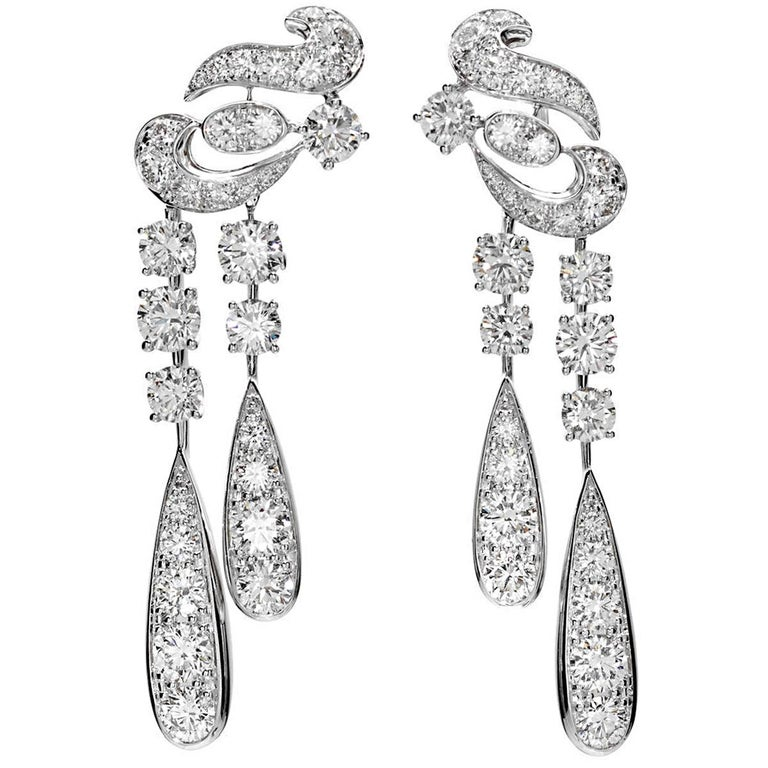 An incredible pair of Graff earrings designed in a swirl motif and suspending diamond drops with the finest Graff round diamonds weighing appx 10.65cts. The earrings are mounting in shimmering 18k white gold and measure 2.37