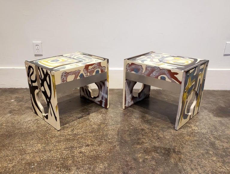 All-over abstract composition hand painted in acrylic and spray-paint by artist Lionel Lamy on a pair of 1970s teak wood, low nightstands. Nightstands have decorative cut-outs, metal veneer elements and one pull out drawer each. Meant to be paired