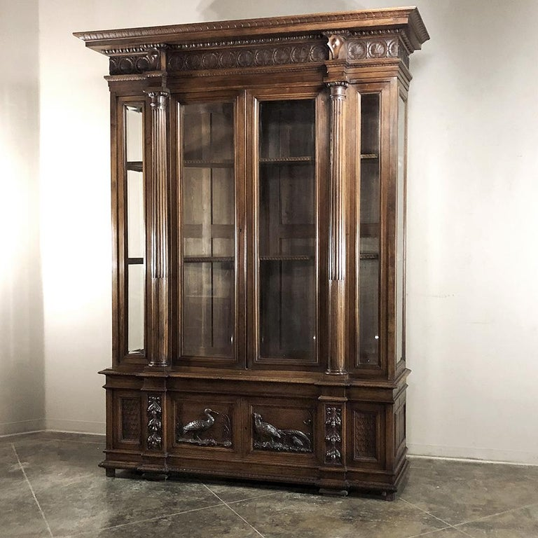 Grand 19th Century Italian Walnut Neoclassical Bookcase is a study in the artistic sculpture of Northern Italy.  Sculpted in solid, sumptuous walnut, it features wildlife scenes which appear at the bottom door panels in glorious full relief, and the