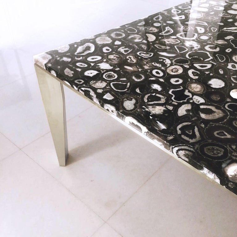 The Grand Architectonic desk/dining table is an elegant piece of furniture art featuring a Black Agate gemstone top with a brushed bronze faceted architectonical base that plays on the unity between structural form and space.   The agate top piece