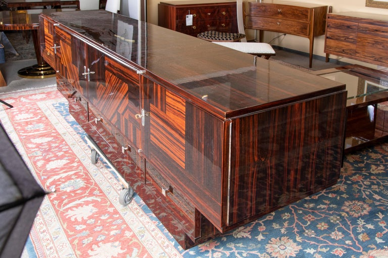 Sideboard has exceptional inlaid wood work that is proudly displayed on the front of the sideboard. Sideboard is made out of 3 rectangular forms that are placed one on top of other. Upper part has 4 large and the middle part has 5 smaller drawers.