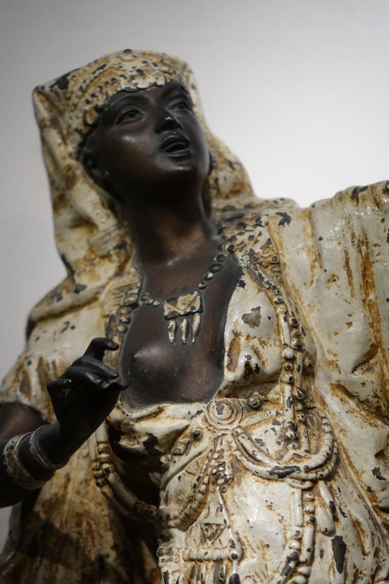 Large Babbit metal statue a woman dressed as an Egyptian, a bare breast, showing part of a deck of cards, the rest of which is on the sideboard at her feet.  We have the impression here of a fortune teller in an Egyptian costume, somewhere in the