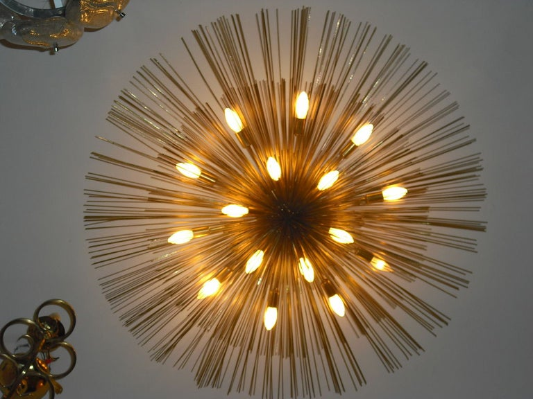 A wonderful thirteen-light brass three-tier flush mounted light sculpture composed of golden aged brass and enameled steel rods. Restored. Rewired. We can drop it on an extended ceiling pole if needed. Pair available.