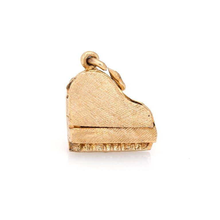 Finely detailed grand piano charm crafted in 14k yellow gold.    The unique charm features lifelike detail of a grand piano (the top opens!). The bale measures 3mm and can accommodate a thin to medium thickness chain if desired. Small in scale the