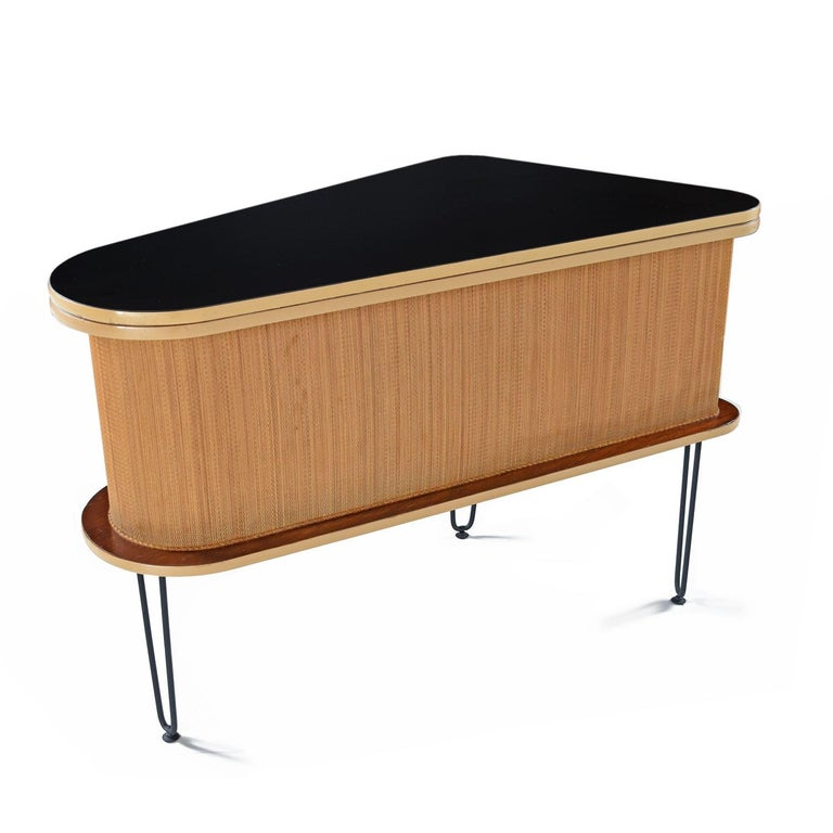 Showcased at the 1963 World's Fair in New York City as an example of modern furniture, the grand server features ingenious midcentury design. The brand new flat black laminate tabletop slides open on a layer of felt. Simply pull up the exposed