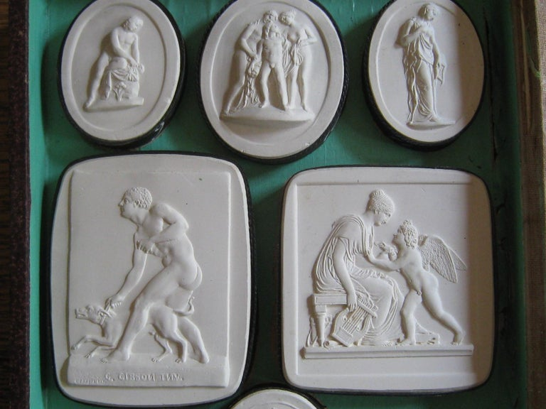 Original set Grand Tour plaster intaglios, 'Opere di Gibson' circa 1830. The set is housed in a double-sided box designed as a book with half marbled boards with gilt lettered vellum spine, speckled 'page edge'. Inside the front and back cover is a
