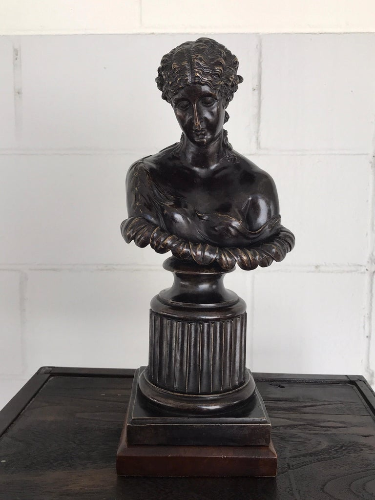 Grand Tour Style bronze bust of Clytie, after the antique, the nymph with downcast face and scantily draped, cupped in a large flower. Raised on a 6