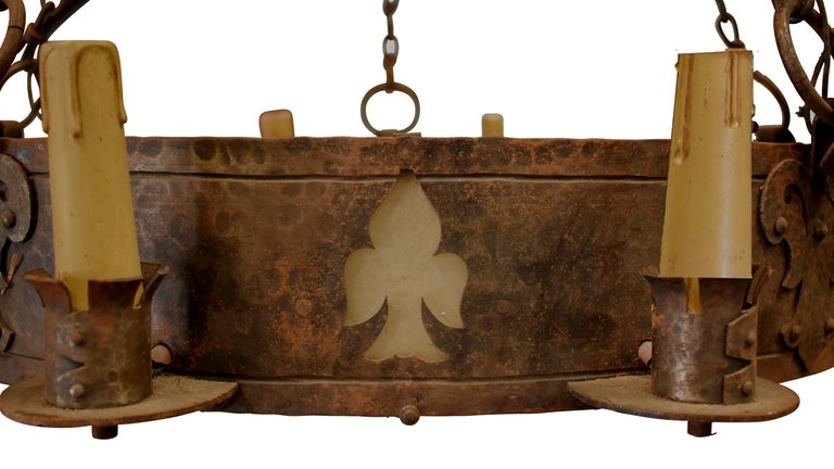 Large vintage hand-forged iron chandelier brings light and a strong statement to a room. Fleur de Lis cutouts and bracket details give added interest. European wiring – will need to be rewired.  This chandelier could be 19th Century but marked it